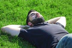 Мужчина лежа на траве стоковые изображения