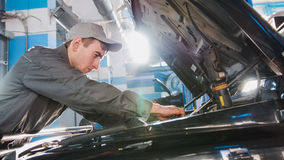 Мужчина механика в гараже автомобиля проверяя клобук автомобиля для роскоши SUV Стоковая Фотография
