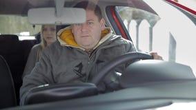 Мужчина паркует автомобиль с белокурой девушкой в заднем сиденье видеоматериал