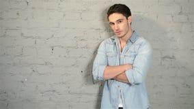 Мужчина представляя в джинсовой ткани и белой футболке акции видеоматериалы