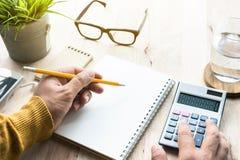 Мужчина работая с калькулятором и блокнотом на worktable Стоковая Фотография