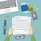 Мужчина  работа с документами Руки ` s людей держат учет, зарплату, налоговую форму Взгляд сверху рабочего места Стоковое фото RF