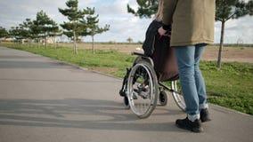 Мужчина свертывает инвалидный стул с молодыми больными outdoors, задней частью и взглядом со стороны женщины акции видеоматериалы