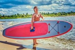 Мужчина серфера с мышечным телом с его surfboard на пляже Стоковые Изображения RF