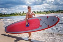 Мужчина серфера с мышечным телом с его surfboard на пляже Стоковые Изображения