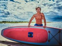 Мужчина серфера с мышечным телом с его surfboard на пляже Стоковое фото RF