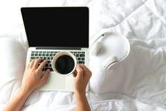 Мужчина сидя на интернете белой кровати занимаясь серфингом или работая на компьтер-книжке и слушая к музыкальным средствам массо Стоковые Изображения