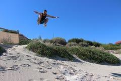 Мужчина скача с песчанных дюн на пляже Cottesloe Стоковое Изображение RF