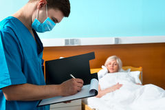 Мужчина сконцентрировал доктора в форме нося маску делая некоторый n Стоковые Фото