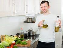 Мужчина с бутылкой оливкового масла стоковое изображение