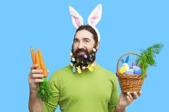 Мужчина с морковами пасхи на голубой предпосылке Стоковая Фотография