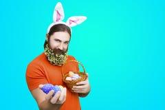 Мужчина с пасхальными яйцами на голубой предпосылке Стоковое Изображение RF