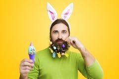 Мужчина с пасхальными яйцами на желтой предпосылке Стоковые Изображения