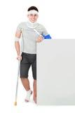 Мужчина с сломленный представлять руки и костыля Стоковое Фото