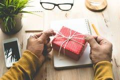 Мужчина украшая милые настоящие моменты подарочной коробки на worktable Стоковые Фотографии RF