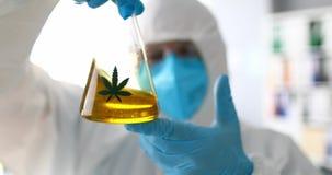 мужчина-химик смешивает желтую жидкость sbd масляный стаксель сток-видео