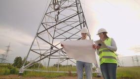 Мужчина электрика и женский в полях около линии передачи энергии Он электрик который управляет акции видеоматериалы