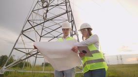 Мужчина электрика и женский в полях около линии передачи энергии Он электрик который управляет видеоматериал