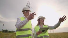 Мужчина электрика и женский в полях около линии передачи энергии Он электрик который управляет сток-видео