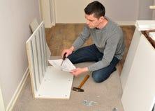 Мужчина Atractive собирая кухонный шкаф - инструкции чтения стоковое фото