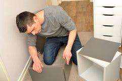 Мужчина Atractive собирая кухонный шкаф стоковая фотография
