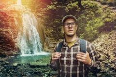 Мужчина Backpacker стоя и смотря вверх около концепции назначения перемещения путешествием водопада Стоковые Изображения