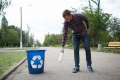 Мужчина Litttering Пустая пластичной выпивая бутылки засаривая на поле дороги Концепция охраны окружающей среды Стоковое Изображение RF
