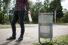 Мужчина Litttering Пустая пластичной выпивая бутылки засаривая на поле дороги Концепция охраны окружающей среды Стоковые Фото