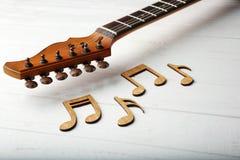 Музыкальные примечания и шея гитары на белой предпосылке стоковые изображения rf