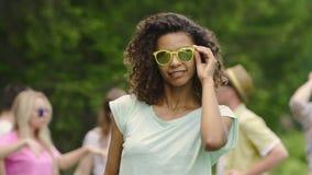 Музыкальный фестиваль, солнечные очки красивой девушки нося и flirting с камерой акции видеоматериалы