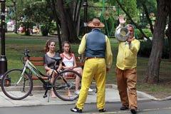 Музыканты улицы играют для девушек в парке взморья Стоковое Изображение RF