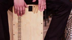 Музыкант барабанщика играет ударный инструмент Cajon Отснятый видеоматериал на музыкальной теме сток-видео