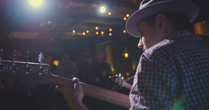 Музыкант - гитарист в шляпе играет гитару в ночном клубе, вид сзади стоковая фотография