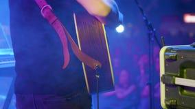 Музыкант двигая в ритм музыки и поет на акустической гитаре акции видеоматериалы