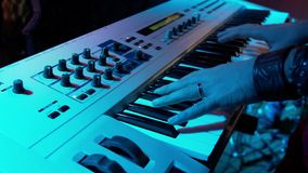 Музыкант играет синтезатор в ночном клубе под покрашенными фарами Мужской клавишник выполняет на партии видеоматериал