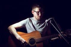 Музыкант играя акустическую гитару и поя стоковые изображения
