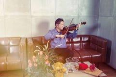 Музыкант играя скрипку в живущей комнате ослабляет время стоковое фото rf