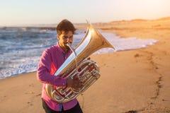 Музыкант играя тубу на музыкальном инструменте морского побережья Стоковая Фотография