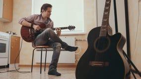 Музыкант молодого человека составляет музыку на гитаре и игры в кухне, другом музыкальном инструменте на переднем плане, Стоковое фото RF