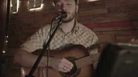 Музыкант поет перед аудиторией смотря прищурясь в текст сток-видео