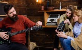 Музыкант с ультрамодной бородой битника и усик играя гитару Музыкальный инструмент бородатого человека настраивая Мама и дочь Стоковая Фотография RF