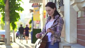 Музыкант улицы девушки, в рубашке, играя гитару медленный mo акции видеоматериалы