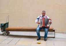 Музыкант улицы играя мелодии с его старым аккордеоном стоковая фотография rf