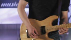 Музыкант утеса играет желтую электрическую гитару, на этапе с покрашенным светом акции видеоматериалы