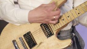 Музыкант утеса играет желтую электрическую гитару, на этапе с покрашенным светом видеоматериал