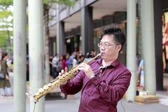 Музыкант улицы играя саксофон в городе Тайбэя Стоковое Фото