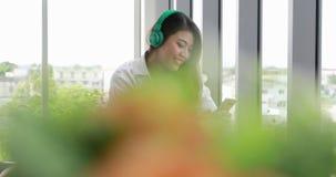 Музыка азиатской женщины слушая от ее смартфона акции видеоматериалы