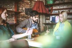 Музыка для души 3 друз на кафе Стоковая Фотография