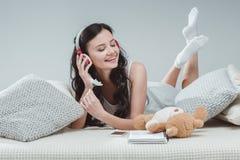 Музыка девушки брюнет слушая в наушниках пока лежащ на софе Стоковые Фотографии RF