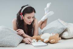 Музыка девушки брюнет слушая в наушниках пока лежащ на софе Стоковые Фото